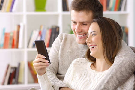 Happy couple using a smart phone sitting on a couch at home in winter