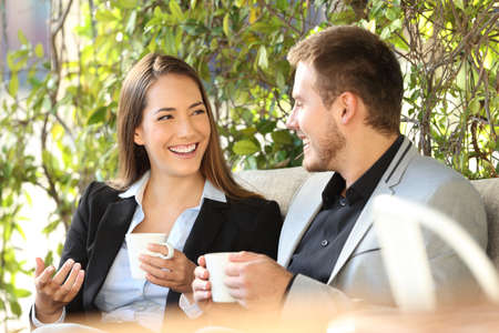 Two happy executives talking in a coffee break sitting in a bar terrace