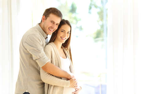 Portrait of a pregnant woman and husband looking at camera standing at home Stock Photo - 88348235