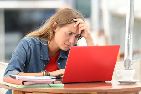 Kies ongerust gemaakte student uit die online inhoud in een laptop zitting in een koffiewinkel zoeken Stockfoto