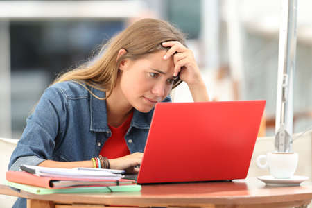Tudiant inquiet unique recherche sur le contenu de la ligne dans un ordinateur portable assis dans un café à l'extérieur Banque d'images - 88348238