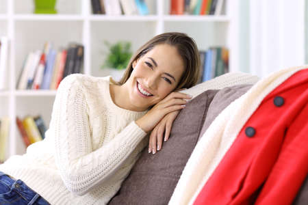 Happy woman posing sitting on a sofa in winter at home Stock Photo