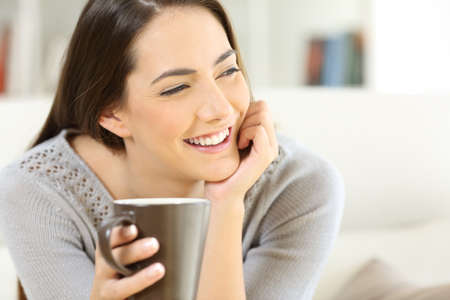 Happy woman holding a cup of coffee and looking away sitting on a couch at home