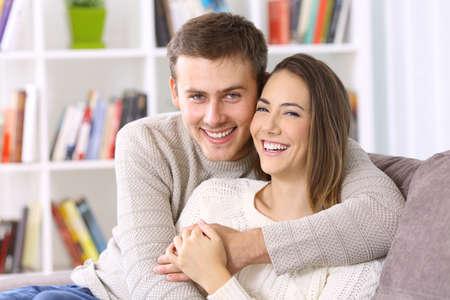 Portret van een gelukkig paar poseren samen dragen van truien kijken camera op een bank thuis in de winter Stockfoto