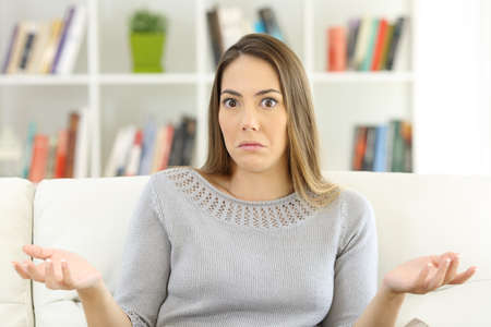 Front view of a doubtful woman shrugging shoulders and looking at you sitting on a sofa at home