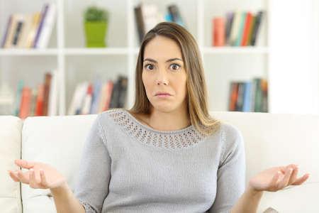 Vorderansicht einer zweifelhaften Frau, die Schultern zuckt und Sie das Sitzen auf einem Sofa zu Hause betrachtet