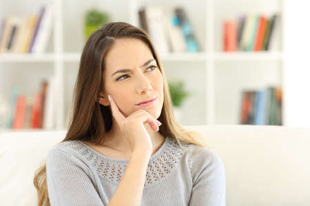 Front view portrait of a woman wondering sitting on a sofa at home Stock Photo