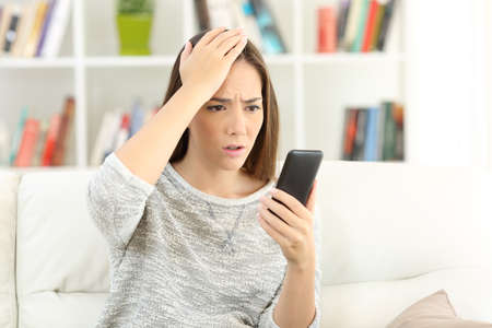 Portrait of a worried woman making mistake on a smart phone sitting on a sofa at home Stock Photo