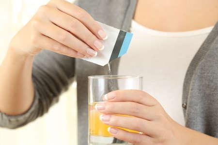 水のガラスの粘液溶解薬袋薬を準備する女性のクローズ アップ