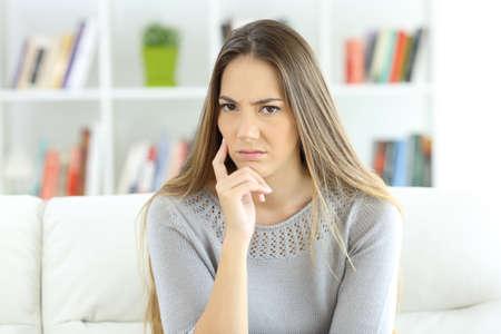 Vooraanzichtportret van een verdachte vrouw die camerazitting op een bank thuis bekijken
