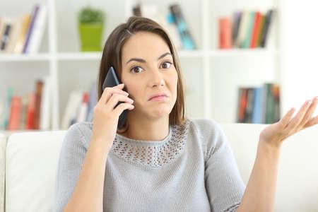 Cliente confuso sendo ignorado ligando para o serviço personalizado e olhando para você sentado em um sofá em casa Foto de archivo - 88672618