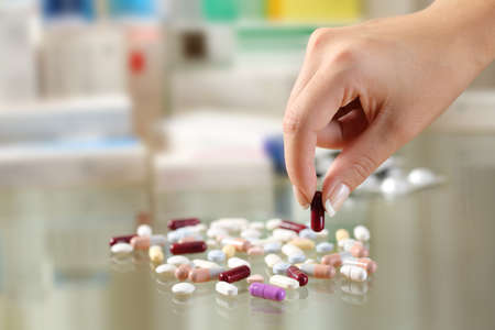 Close up of a woman hand catching a pill from a group of medicines on a glass table