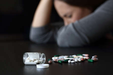 Close up of a depressed woman beside a lot of pills on a table on a dark background Stock fotó