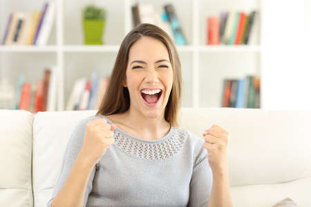 Front view portrait of an excited woman looking at camera sitting on a sofa at home