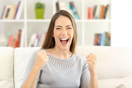 Vooraanzichtportret van een opgewekte vrouw die camerazitting op een bank thuis bekijken Stockfoto