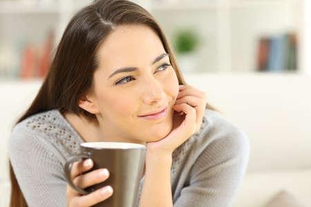 物思いにふける女性側の自宅のリビング ルームでソファの上に座って見てコーヒー カップを保持しています。 写真素材