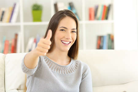 Satisfied home owner looking at you with thumbs up sitting on a couch at home Фото со стока