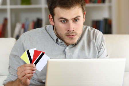 Stressed compulsive gambler gambling on line sitting on a sofa at home Stock Photo