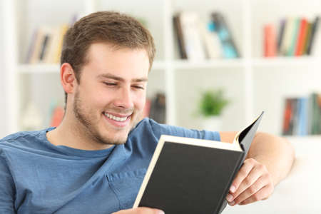 Happy guy reading a paper book sitting on a sofa at home Foto de archivo