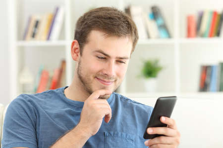 Man dating on line with a smart phone sitting on a sofa at home Stock Photo