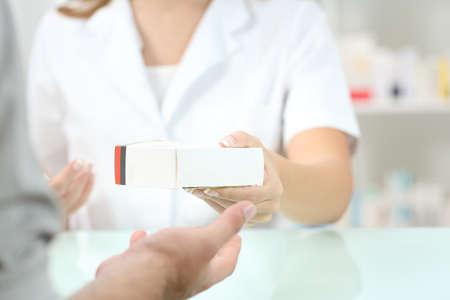 顧客に薬物を与える薬剤師手のクローズ アップ