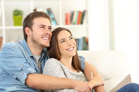 Szczęśliwa para marzy patrzeć above siedzieć na kanapie w żywym pokoju w domu