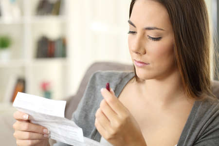 Serious woman holding a medicine capsule reading a leaflet sitting on a sofa in a house interior Stock Photo