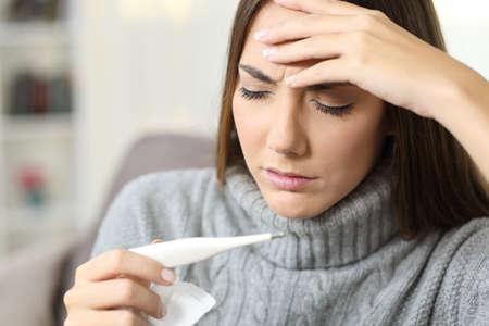 Mujer enferma con jersey de control de temperatura del termómetro sentado en un sofá en la sala de estar en el interior de una casa