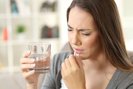 Pijnlijke vrouw die een pillenzitting op een bank in de woonkamer in een huisbinnenland neemt Stockfoto - 89097059