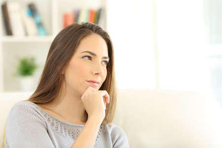 Portrait of a pensive woman wondering looking through a window sitting on a sofa in the living room at home with copy space in white Stock Photo
