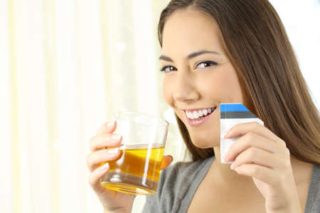 Happy woman posing holding a glass of soluble orange liquid medicine in a house interior