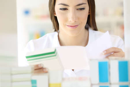 Front view portrait of a pharmacist reading prescription and preparing medicines in a pharmacy