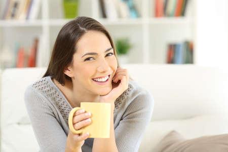 Mujer feliz posando mirando cámara de arte sosteniendo una taza de café sentado en un sofá en casa Foto de archivo - 89097092