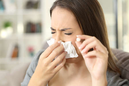 Woman coughing covering mouth with a tissue and holding a pill sitting on a sofa in a house interior