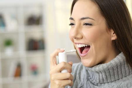 Mulher feliz vestindo jérsei usando um spray analgésico para suavizar a garganta sentado em um sofá em um interior de casa