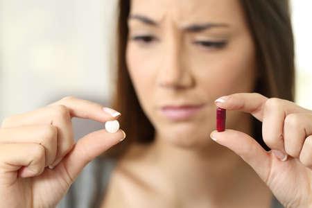 Portret van een vrouw die over pil of capsule in een huisbinnenland benieuwd zijn