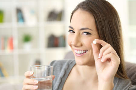 Happy woman holding a white round pill and a glass of water looking at camera sitting on a sofa in a house interior