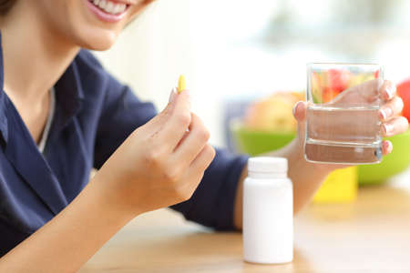 Close up of a woman hand holding omega vitamin 3 pill on a table at home with a colorful background Banco de Imagens