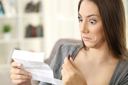 Shocked woman reading contraindications of a leaflet of a red capsule sitting on a sofa in a house interior