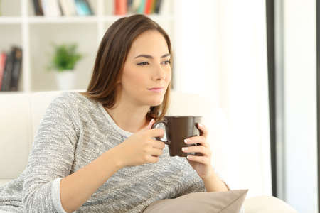 Portrait of a pensive girl holding a cup of coffee sitting on a sofa at home Stock Photo