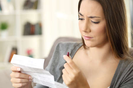 Woman reading a leaflet before taking a red pill sitting on a sofa in the living room in a house interior