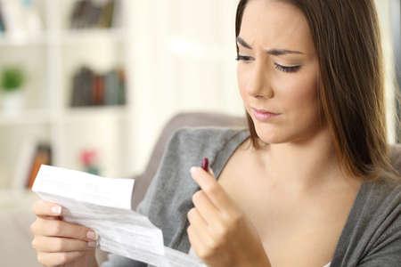 Mujer leyendo un folleto antes de tomar una pastilla roja sentado en un sofá en la sala de estar en el interior de una casa