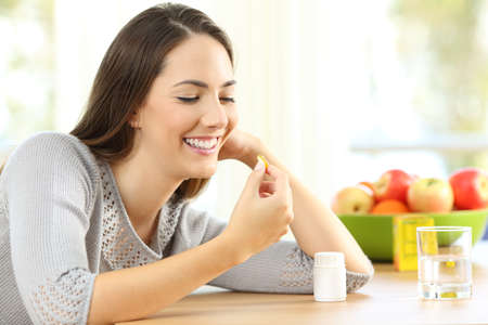 Happy woman taking omega 3 vitamin pills on a table at home with a colorful background Stock Photo