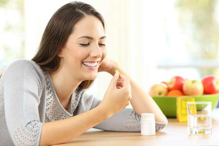 Mujer feliz tomando píldoras de vitaminas omega 3 en una mesa en casa con un fondo colorido Foto de archivo - 89108330