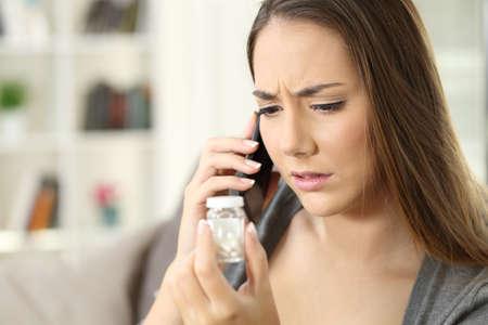 Chica preocupada pidiendo información sobre medicamentos sentado en un sofá en la sala de estar en el interior de una casa Foto de archivo