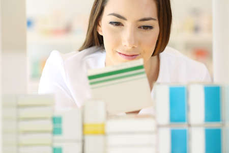 Front view of a pharmacist searching medicines in a pharmacy interior