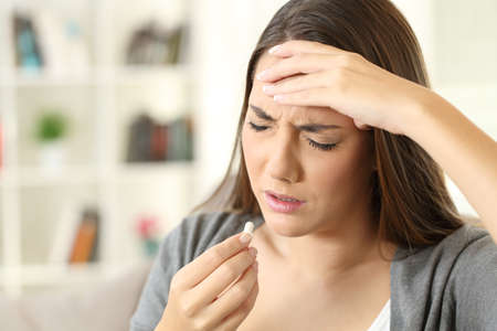 Ill woman suffering headache taking a pill sitting on a sofa in a house interior