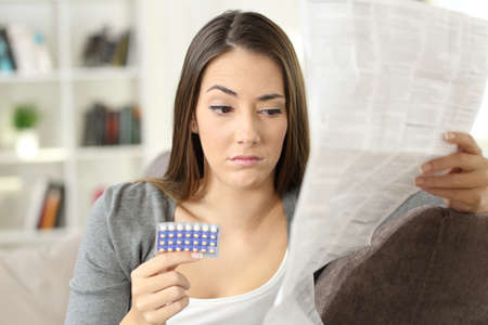Suspicious woman reading a leaflet after taking contraceptive pills sitting on a couch in the living room in a house interior