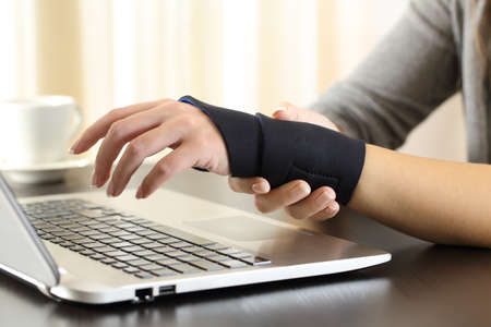 Close up of a woman hands with injured wrist complaining using a laptop at home