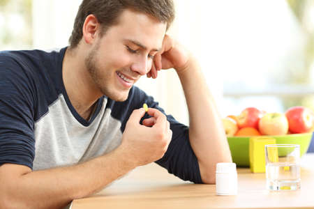 Happy man taking a yellow omega 3 vitamin pill on a table at home